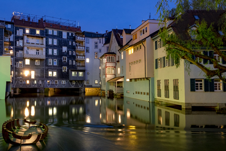 Night shot of the historic quarter Small Venice in Esslingen with the Neckar river and an old wreck in the foreground. Stock Photo