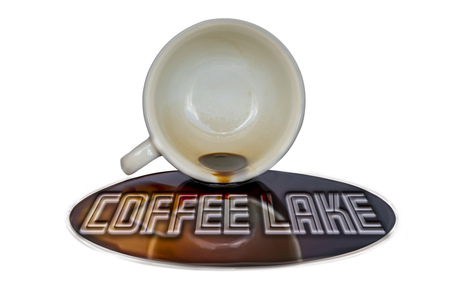 Overturned cup of coffee with writing coffee lake in the puddle