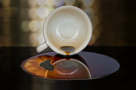 Overturned cup of coffee with puddle Stock Photo