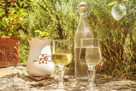 Cover of fresh ordinary table wine with rustic pitcher and bottle of water, served in south italy. The glasses are filled with white wine and water.