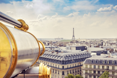Cityscape of Paris with historic telescope in the foreground.