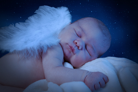 Cute newborn with wings sleeps on cuddly blanket. Night interpreted scene with stars.