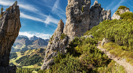 Panorama photo of the Dolomites mountains high altitude trail among group of rocks.