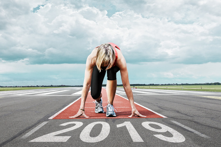 Female runner waits for her start at an airport runway. In the foreground the painted date 2019 symbolises the year. Stock Photo