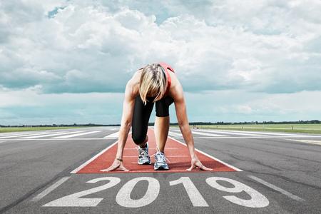 Läuferin wartet auf ihren Start auf einer Landebahn eines Flughafens. Im Vordergrund symbolisiert das aufgemalte Datum 2019 das Jahr. Standard-Bild