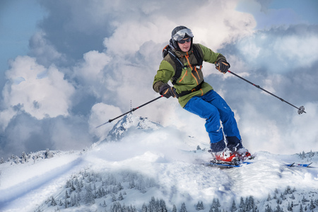 Composing of apparantly giant back country skier, who rides the snowcapped mountains. Фото со стока