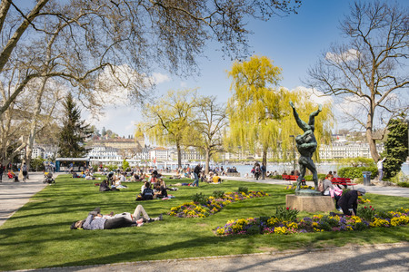 LUCERNE, SWITZERLAND- APRIL 19, 2019: People relaxing at Inseli park Lucerne, enyoing the spring sun. Редакционное