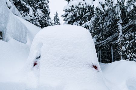 Snow covered car standing in a  parking lot.