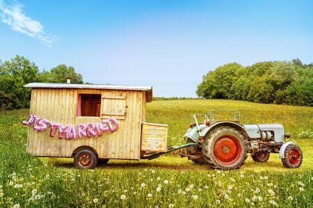 """Szenisch platzierter Holzanhänger mit Traktor und rosa """"Just Married"""" Textballons auf blumenbedeckter Wiese, die eine glückliche Ehe ankündigen. Standard-Bild"""