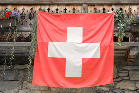 Swiss flag hanging on facade of traditional build swiss house.