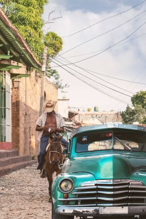 Parking classic car in Cuba with horse rider approaching . Фото со стока