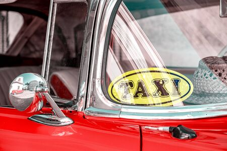 Historic american car in Havana with taxi sticker on windshield and straw hat lying on the dashboard