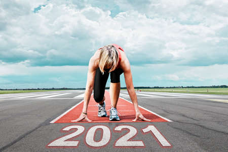 Female runner waits for her start at an airport runway. In the foreground the painted date 2021 symbolizes the year.