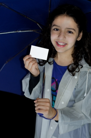 Child with raincoat and umbrella showing a white greeting card photo