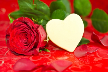 red rose bokeh: A white shaped chocolate heart with a rose