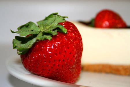Close up of a strawberry and a cheesecake on a plate. photo
