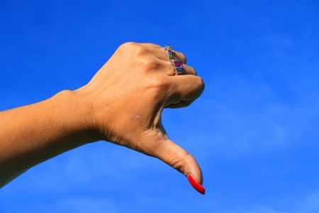 Womans hand showing thumb down sign over blue sky. photo