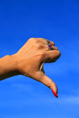 Woman's hand showing thumb down sign over blue sky. Stock Photo - 2644963