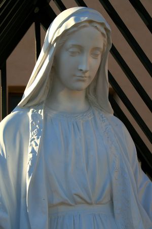 Statue of a Virgin Mary next to a church. photo