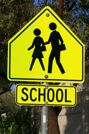 xing: Bright school crossing road sign close up.
