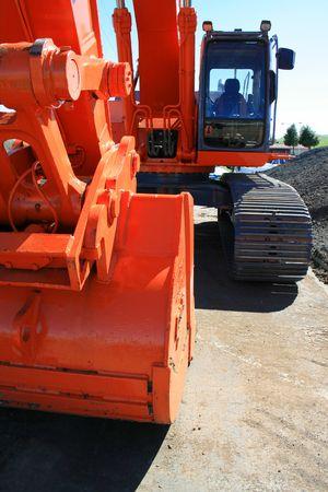 Orange excavator close up on a construction sight.