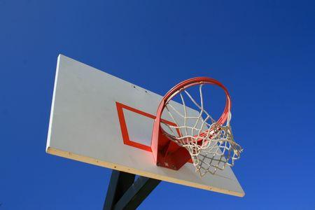 backboard: Basketball net and backboard over clear blue sky.