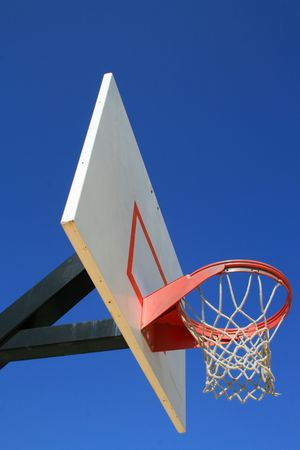Basketball net and backboard over clear blue sky. photo