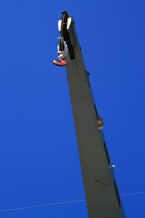 Industrial hook hanging over clear blue sky.