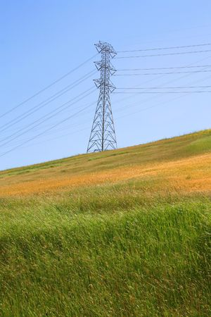Electricity pylon on a hill over clear blue sky.  photo