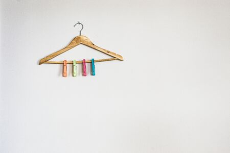 hanger with colorful clothespins on white wall Stock Photo