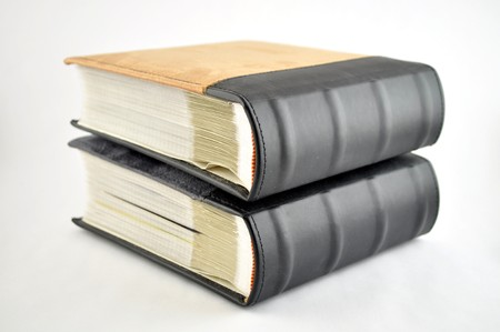Two leather bound books stacked on a white background