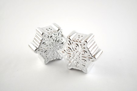 Silver salt and pepper shakers in the shape of snowflakes