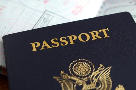 バック グラウンドで別のスタンプのパスポートを持つ米国のパスポートのショットを閉じる