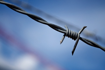 Up close shot of barbed wire on a fence of a construction site Stock Photo