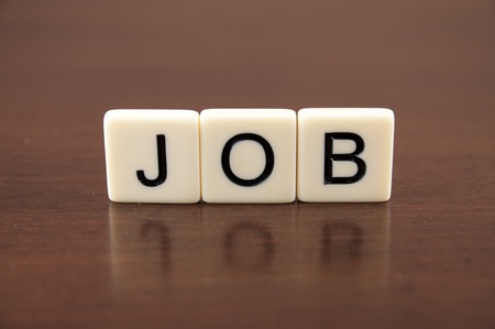 JOB spelled from letter tiles on a wooden background