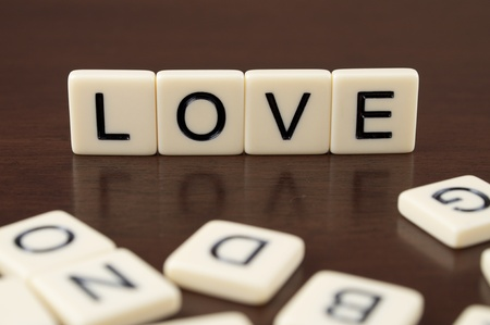 LOVE spelled from letter tiles on a wooden background Stock Photo