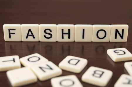 FASHION spelled from letter tiles on a wooden background Stock Photo
