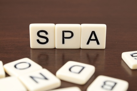 SPA spelled from letter tiles on a wooden background Stock Photo