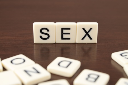 SEX spelled from letter tiles on a wooden background Stock Photo