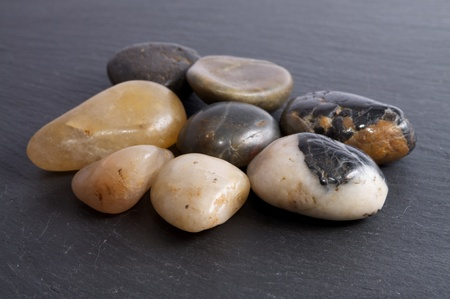 Group of river stones on a black slate background Фото со стока