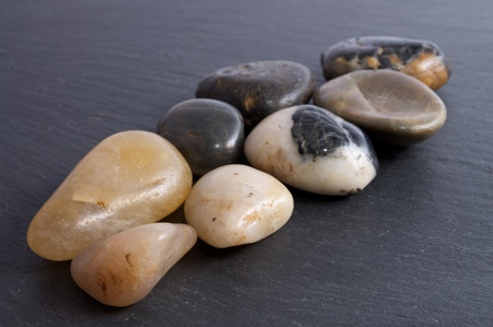 Group of river stones on a black slate background Stock Photo