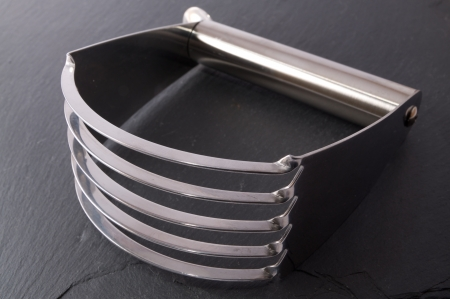 Stainless steel pastry blender on a slate background