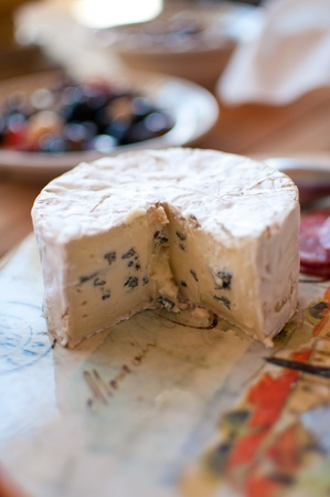 Small wheel of bliue brie on a tuscan cutting board Banco de Imagens - 9233205