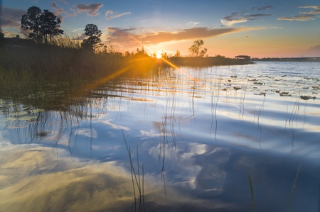 Sunset on a lake with reflection of sky in the water Reklamní fotografie