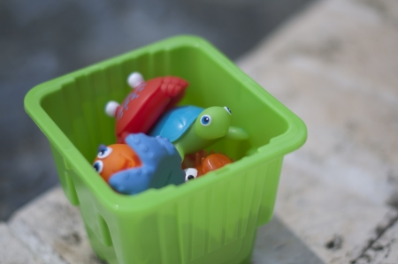 Pool toys in a green bucket Stock Photo