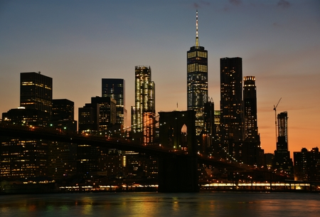 The Brooklyn Bridge and skyline of downtown Manhattan from Brooklyn at sunset.