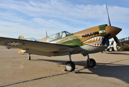 A vintage World War II-era Curtiss P-40 Warhawk fighter plane on the runway