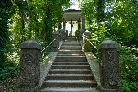 Staircase in the middle of nature area, leading to a Christian sanctuary with three sculptures of Jesus Christ crucified, in Kapuzinerberg hill. Salzburg, Austria