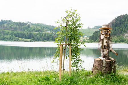 Dedinky, Roznava, Kosice region / Slovakia - June 20, 2018:  statue of a character smoking a pipe on a lake