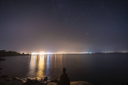 Night landscape from a cove on the outskirts of the urban center of s'Estanyol in Mallorca, starry night and light pollution, and a seated man contemplating the beauty of the nigh Stok Fotoğraf